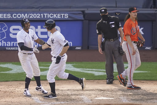 New York Yankees' DJ LeMahieu, center left, scores the winning run on an RBI sacrifice fly by Luke Voit off Baltimore Orioles relief pitcher Hunter Harvey, right, in the 10th inning of a baseball game, Saturday, Sept. 12, 2020, in New York. (AP Photo/John Minchillo)
