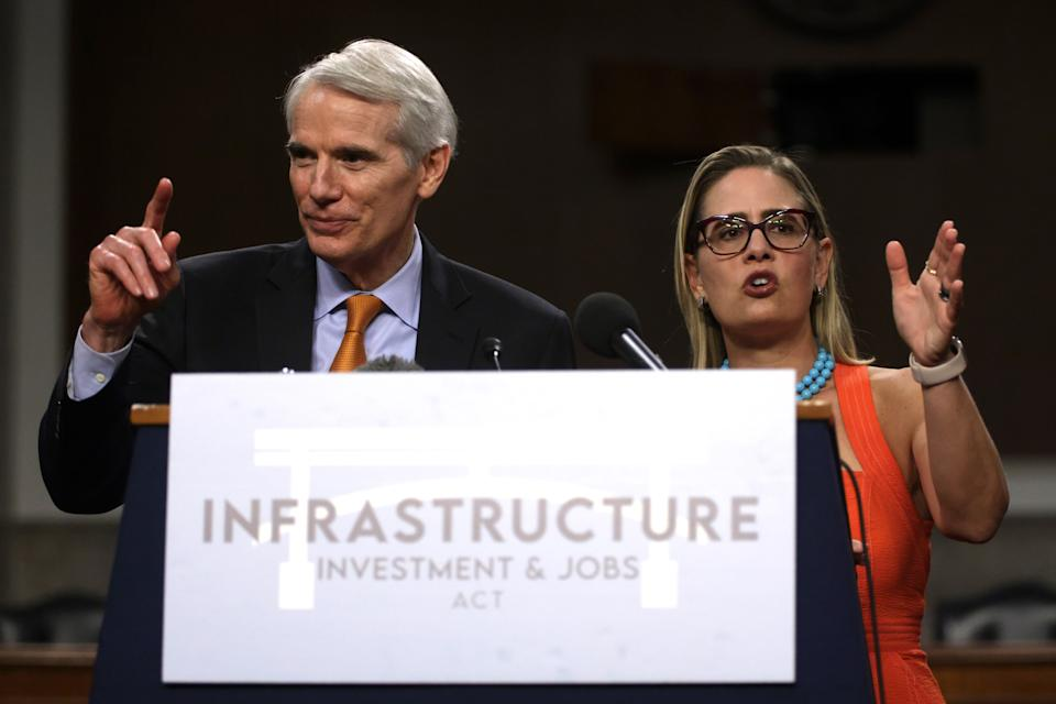 WASHINGTON, DC - JULY 28:  U.S. Sen. Rob Portman (R-OH) (L) and Sen. Kyrsten Sinema (D-AZ) (R) answer questions from members of the press during a news conference after a procedural vote for the bipartisan infrastructure framework at Dirksen Senate Office Building July 28, 2021 on Capitol Hill in Washington, DC. The Senate has advanced the bipartisan infrastructure framework with the vote of 67-32. (Photo by Alex Wong/Getty Images)