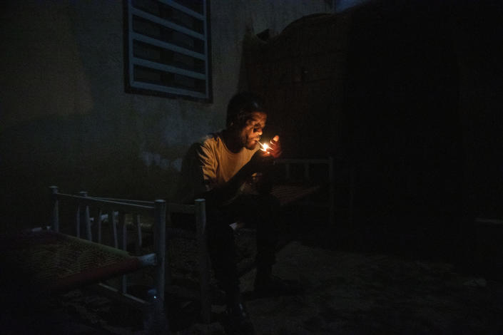 Surgeon and doctor-turned-refugee, Dr. Tewodros Tefera, lights a cigarette and rests on his bed after finishing his work, at the Sudanese Red Crescent clinic in Hamdayet, eastern Sudan, near the border with Ethiopia, on March 22, 2021. (AP Photo/Nariman El-Mofty)