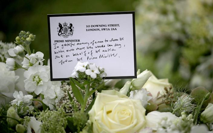 A wreath sent by prime Minister Boris Johnson among the flowers outside St George's Chapel, at Windsor Castle, - PA