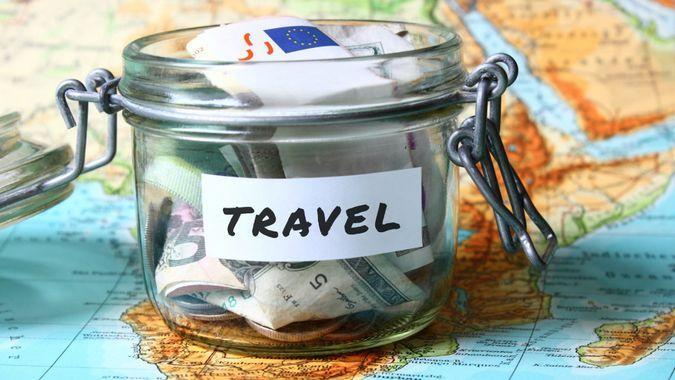 Travel budget - vacation money savings in a glass jar on world map.