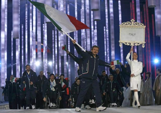 Italy's flag-bearer Andrea Chiarotti (C), leads his country's contingent during the opening ceremony of the 2014 Paralympic Winter Games in Sochi, March 7, 2014. REUTERS/Alexander Demianchuk (RUSSIA - Tags: OLYMPICS SPORT)