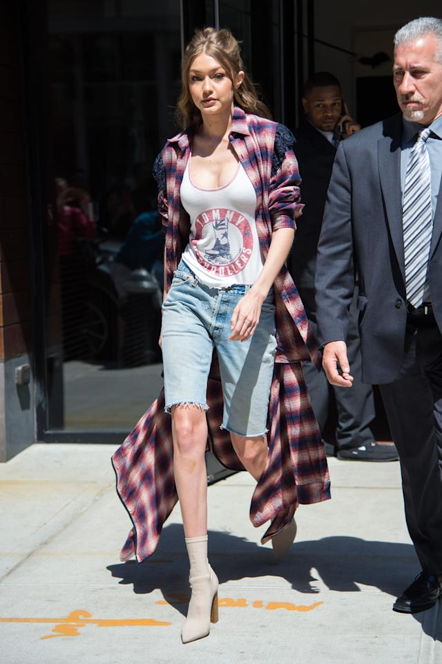 <p>In a flannel cardigan, Tommy Hilfiger tank top, Bermuda cutoff jean shorts and nude sock boots while out in New York City.</p>