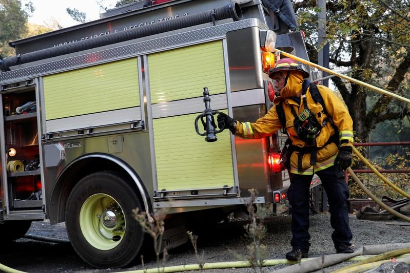 A firefighter passes a hose nozzle while working on a burning structure at the Kincade fire in Calistoga, California