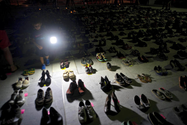 A child shines a light on hundreds of shoes at a memorial for those killed by Hurricane Maria, in front of the Puerto Rico Capitol in San Juan. Puerto Rico has conceded that Hurricane Maria killed more than 1,400 people on the island last year and not just the 64 in the official death toll. (AP Photo/Ramon Espinosa, File)