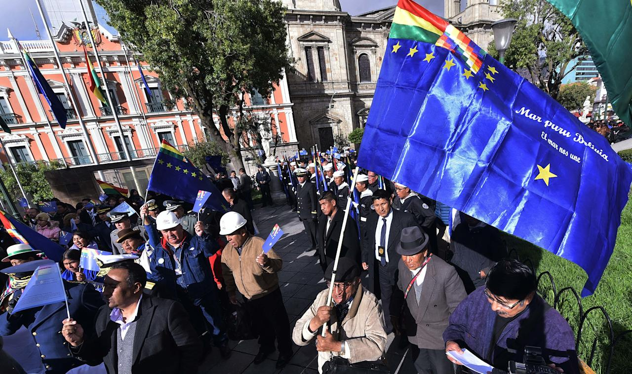 People carrying blue flags representing the Bolivian Navy watch a live transmission of a court session at the International Court of Justice in The Hague, where Bolivia presents its arguments for access to the sea, in Plaza Murillo in La Paz, Bolivia, Monday, March 19, 2018. Bolivia made an emotional appeal for the court to order Chile to enter talks over granting the landlocked South American nation access to the Pacific Ocean, saying the dispute will remain a source of conflict if it's not resolved. Bolivia lost its only seacoast to Chile in a war between from 1879 to 1883. (AP Photo)