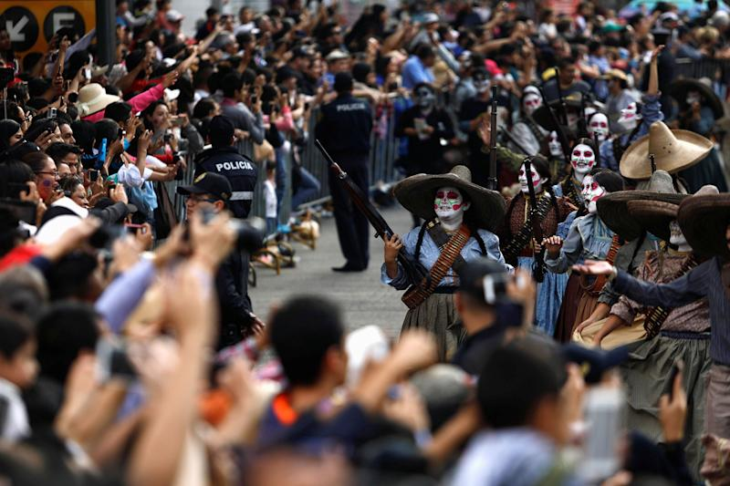 Women participate in a procession to commemorate Day of the Dead in Mexico City on Saturday.