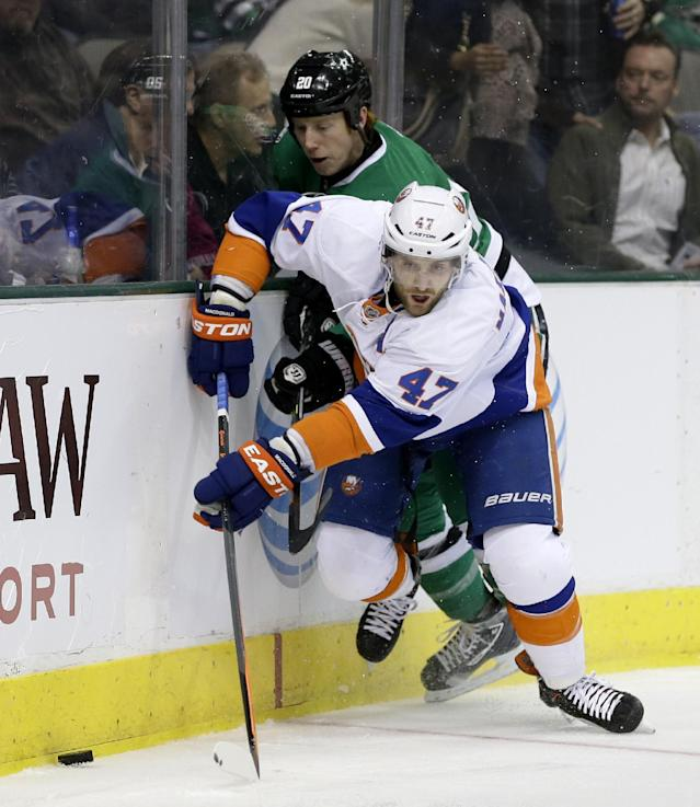 New York Islanders' Andrew MacDonald (47) attempts to gain control of the puck behind the net as Dallas Stars' Cody Eakin, rear, pressures in the first period of an NHL hockey game, Sunday, Jan. 12, 2014, in Dallas. (AP Photo/Tony Gutierrez)