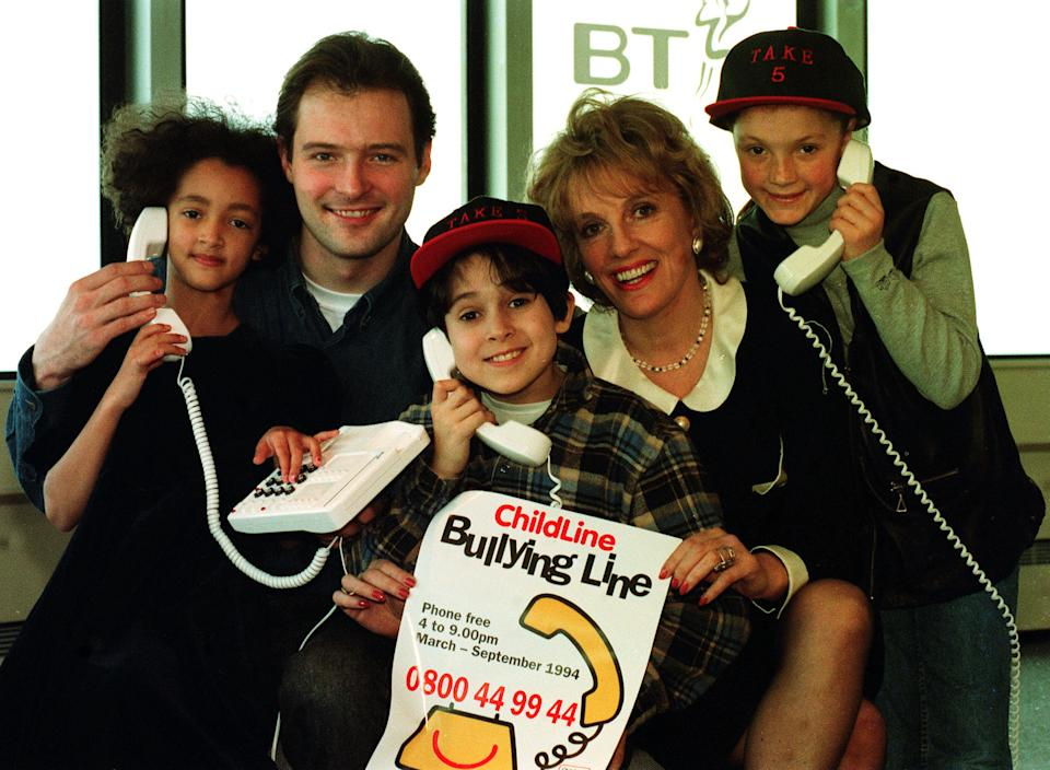 Blue Peter presenters John Leslie and That's Life presenter Esther Rantzen with (left to right) Justine Johnson, 7, Rahul Bery, 8, and Jamie Buckingham, 10, at the launch of a telephone helpline for the victims of bullying at the BT tower. (Photo by Fiona Hanson - PA Images/PA Images via Getty Images)