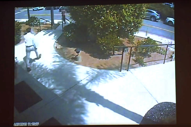 This April 27, 2019 photo from surveillance video at the Chabad of Poway, shown as evidence in the preliminary hearing of John T. Earnest, shows what authorities say is Earnest fleeing, in the street at top left, being pursued by Oscar Stewart, a combat veteran of Iraq and the first Gulf War, left center, after his rampage on the synagogue in Poway, Calif., in court in San Diego, Calif. on Thursday, Sept. 19, 2019. A woman was killed and three other people were wounded in the attack. Earnest has pleaded not guilty to murder, attempted murder and arson tied to a mosque fire. (Chabad of Poway/San Diego Superior Court via AP)
