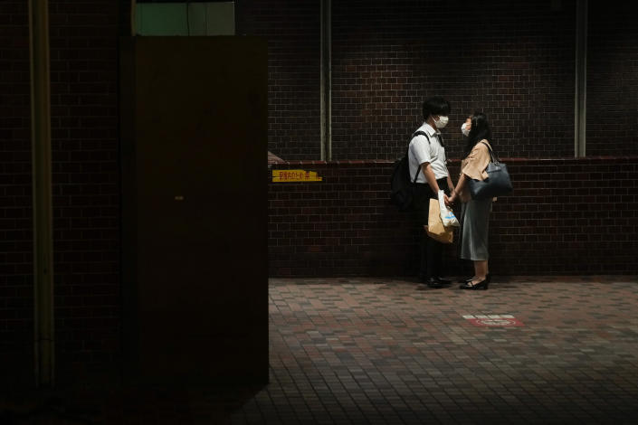 A couple hold hands at a subway station ahead of the 2020 Summer Olympics on Wednesday, July 14, 2021, in Tokyo. (AP Photo/Jae C. Hong)