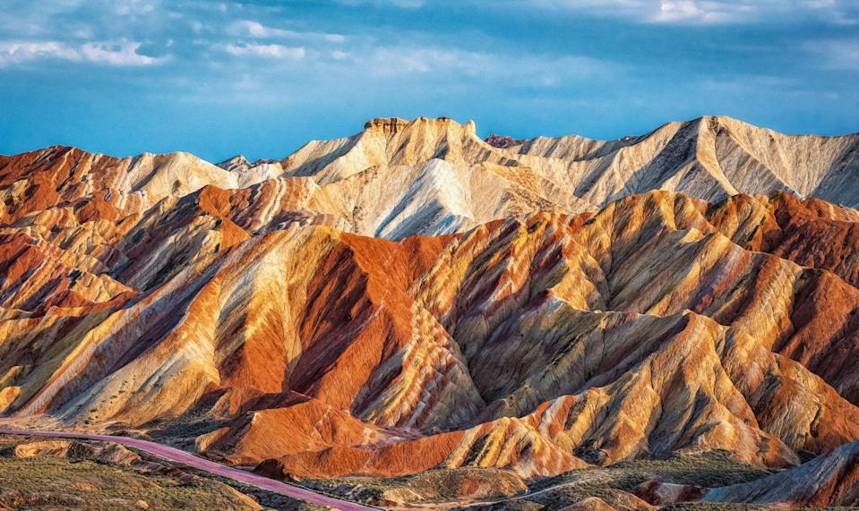 <p>The Danxia landform in Zhangye, China, gets its color from red sandstone and mineral deposits. </p>