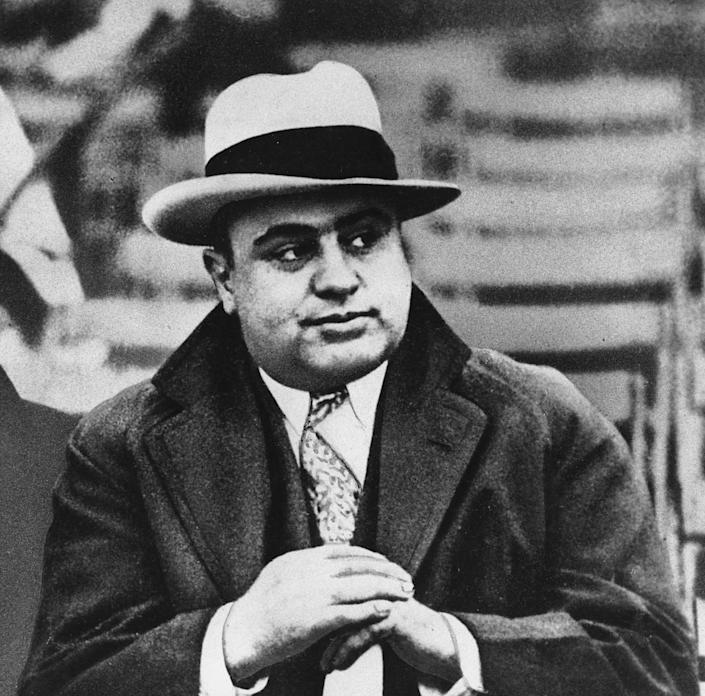 FILE - This Jan. 19, 1931 file photo shows Chicago mobster Al Capone at a football game. The legend of Eliot Ness, portrayed over the years by Kevin Costner and Robert Stack as an incorruptible hero, is now at risk, with some claiming his role in taking out Capone is as mythical as Mrs. O'Leary's cow had to do with starting the Great Chicago Fire. Illinois' two U.S. senators have proposed naming the Bureau of Alcohol, Tobacco, Firearms and Explosives in Washington after Ness, but Ed Burke, a prominent Chicago alderman and others are trying to convince the senators to drop the whole thing. (AP Photo/File)