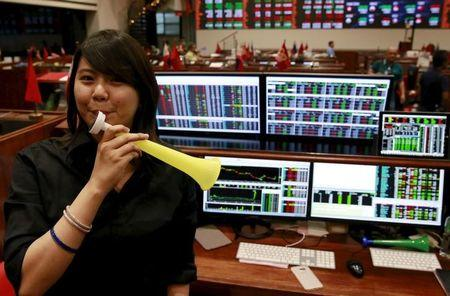 A Filipino trader blows a horn as she poses for the camera inside the Philippine Stock Exchange (PSE) in Makati city, metro Manila December 29, 2015.  REUTERS/Romeo Ranoco/Files