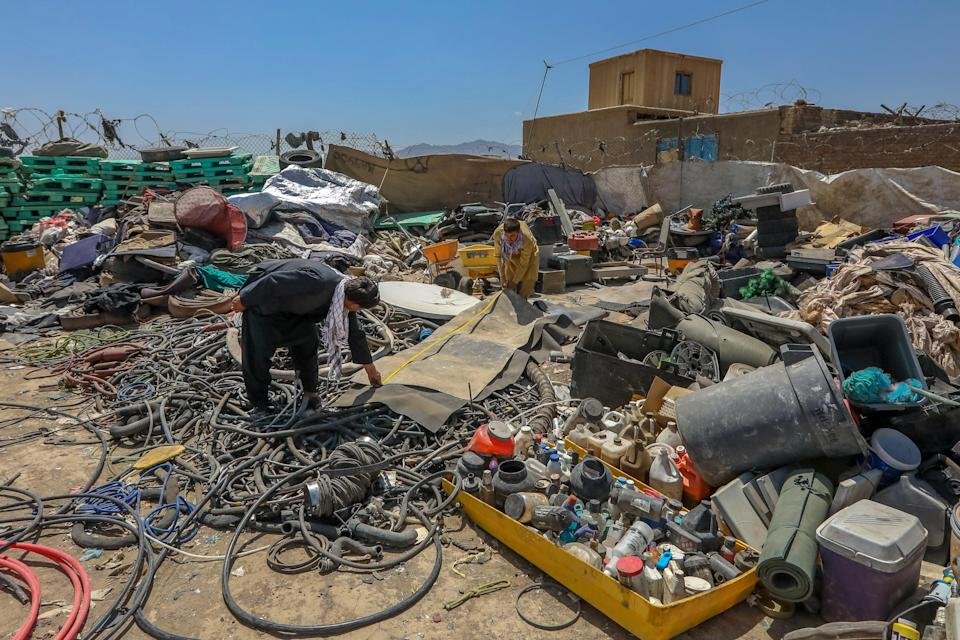 Afghan scrap dealers sort items which were discarded by the US forces outside Bagram Air Base, some 50 kilometers north of the capital Kabul, Afghanistan, 03 July 2021. (EPA)
