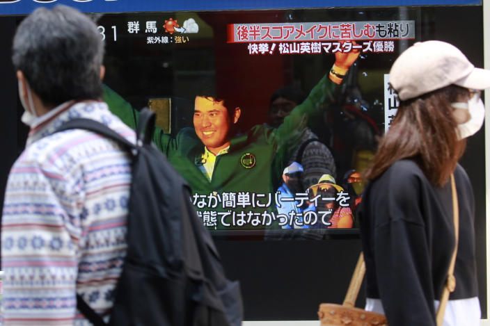 People walk past Japanese golfer Hideki Matsuyama seen in a TV news channel reporting his win in the Masters golf tournament, in Tokyo, Monday, April 12, 2021. From Japan's prime minister on down, the country celebrated Matsuyama's victory in the Masters — the first Japanese to win at Augusta National and wear the famous green jacket.(AP Photo/Koji Sasahara)