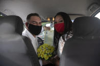 Ayrton, left, and Natasha, wearing masks to prevent the spread of the new coronavirus, pose for a photo after their drive-thru wedding at the registry office in the neighborhood of Santa Cruz in Rio de Janeiro, Brazil, Thursday, May 28, 2020. Couples unable to have a traditional wedding because of the coronavirus pandemic are now taking part in drive-thru weddings. (AP Photo/Silvia Izquierdo)