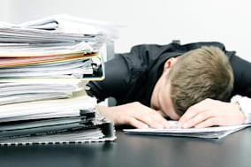 tired office worker and a pile...