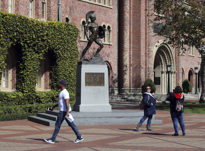 FILE - In this Tuesday, March 12, 2019 file photo, people pose for photos in front of the iconic Tommy Trojan statue on the campus of the University of Southern California in Los Angeles. The university says a review of students possibly connected to a college admissions bribery scandal could lead to expulsions. The university said in a statement Monday, March 18, 2019, it has placed holds on the accounts of those students, which prevents them from registering for classes or acquiring transcripts while their cases are under review. (AP Photo/Reed Saxon,File)