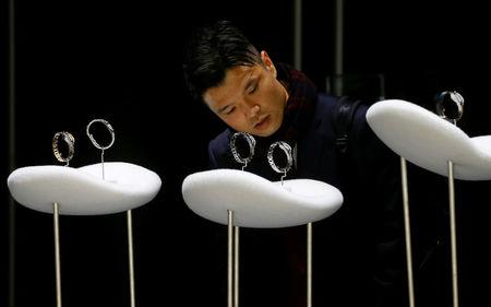FILE PHOTO: A visitor looks at watches at the Baselworld watch and jewellery fair in Basel, Switzerland March 22, 2017. REUTERS/Arnd Wiegmann/File Photo