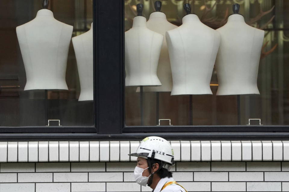 A construction worker wearing a protective mask to help curb the spread of the coronavirus walks past a clothing shop Monday, Nov. 2, 2020, in Tokyo. The Japanese capital confirmed more than 80 new coronavirus cases on Monday. (AP Photo/Eugene Hoshiko)