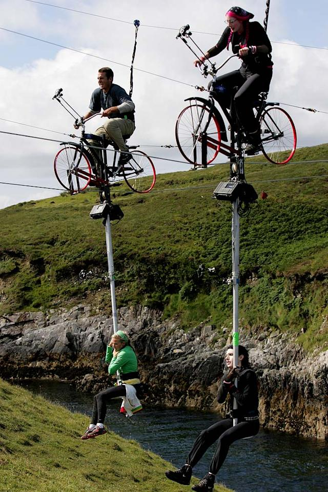 Teammates Nathan and Jennifer (left) and Vyxsin and Kynt (right) perform a Road Block during The Amazing Race 12, in which one team member must transport the other on a high-wire bike over a 400ft windswept ravine, 200ft above jagged rocks, in order to find their next clue.