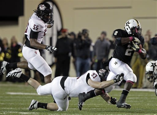 Vanderbilt running back Zac Stacy (2) tries to escape the grasp of Massachusetts defensive lineman Kevin Byrne (93) as defensive lineman Ryan Delaire (55) trails the play in the first quarter of an NCAA college football game Saturday, Oct. 27, 2012, in Nashville, Tenn. (AP Photo/Wade Payne)