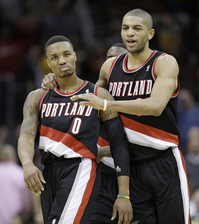 Portland Trail Blazers' Nicolas Batum, left, of France, congratulates Damian Lillard after Lillard scored the game winning basket in the fourth quarter of an NBA basketball game Tuesday, Dec. 17, 2013, in Cleveland. Portland won 119-116. (AP Photo/Tony Dejak)