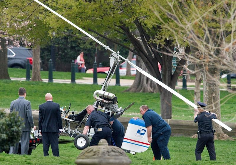 Capitol Hill police officers and other officials lift a gyrocopter that landed on the U.S. Capitol's South Lawn, onto a trailer on April 15, 2015. A man identified as Doug Hughes, 61, illegally landed his aircraft on the Capitol lawn, triggering street closures around the building and prompting a police investigation. Hughes is described as a mailman, and a logo appearing to be that of the U.S. Postal Service was visible on the tail fin of the aircraft.