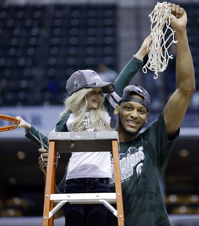 Michigan State forward Adreian Payne, right, hoists the net with Lacey Holsworth, who is battling cancer and has become close to Payne, after Michigan State defeated Michigan 69-55 in an NCAA college basketball game in the championship of the Big Ten Conference tournament on Sunday, March 16, 2014, in Indianapolis. (AP Photo/Michael Conroy)
