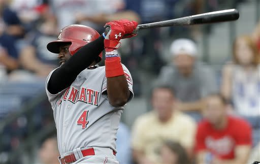 Cincinnati Reds' Brandon Phillips connects with a two-run base hit in the first inning of a baseball game against the Atlanta Braves, Friday, July 12, 2013, in Atlanta. (AP Photo/John Bazemore)