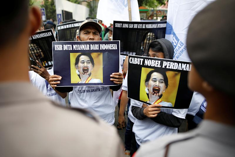 Protesters outside of Myanmar's embassy in Jakarta hold signs protesting Myanmar's government and Aung San Suu Kyi on Sept. 4, 2017.