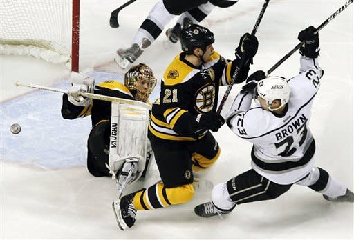 Boston Bruins goalie Tuukka Rask, left, goes down as he protects the net while defenseman Andrew Ference (21) defends against Los Angeles Kings right wing Dustin Brown (23) in the first period of an NHL hockey game in Boston, Tuesday, Dec. 13, 2011. (AP Photo/Elise Amendola)