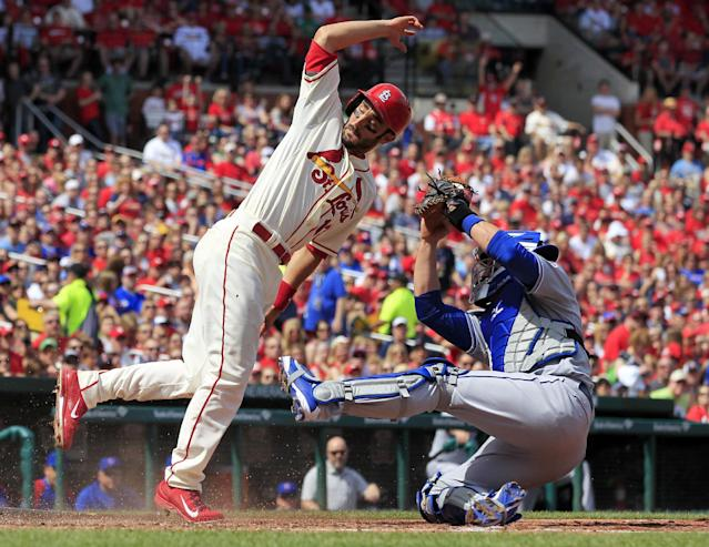 St. Louis Cardinals' Matt Carpenter, left, scores as he avoids the tag from Chicago Cubs catcher John Baker during the fourth inning of a baseball game Saturday, April 12, 2014, in St. Louis. (AP Photo/Jeff Roberson)