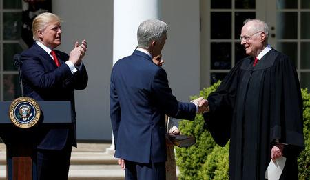 FILE PHOTO: Judge Neil Gorsuch shakes hands with Justice Anthony Kennedy after he was sworn as an Associate Supreme Court as U.S. President Donald J. Trump watches in the Rose Garden of the White House in Washington, U.S. on April 10, 2017. REUTERS/Joshua Roberts/File Photo