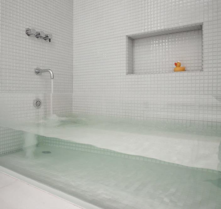 This 'invisible' bathtub, designed by Stern McCafferty Architecture & Interiors, features a thick sheet of glass between two tile walls.… Read more » It reminds us of a fish tank! (Photo: Eric Roth)