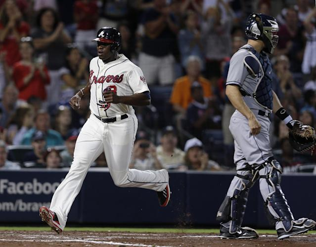 Atlanta Braves' Justin Upton, left, runs past San Diego Padres catcher Nick Hundley, right, to score on a Chris Johnson base hit in the fourth inning of a baseball game in Atlanta, Saturday, Sept. 14, 2013. (AP Photo/John Bazemore)
