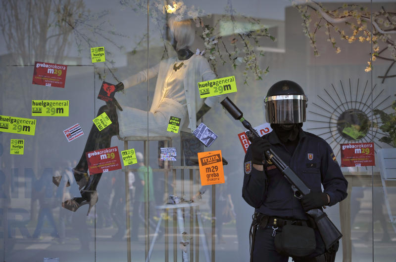 A riot police officer protects a shopping center with the showcase windows covered in stickers calling for a general strike to protest against the government's tough new labor reforms and cutbacks in Pamplona, northern Spain, Thursday, March 29, 2012. Flag-waving Spanish workers livid over labor market reforms they see as flagrantly pro-business blocked traffic Thursday, formed boisterous picket lines outside wholesale markets and bus garages as part of a nationwide general strike against the new conservative government. (AP Photo/Alvaro Barrientos)