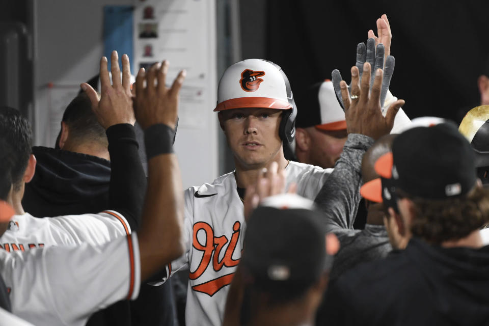 Baltimore Orioles' Ryan Mountcastle is greeted by teammates after hitting a solo home run against Texas Rangers starting pitcher Glenn Otto during the fifth inning of a baseball game, Thursday, Sept. 23, 2021, in Baltimore. (AP Photo/Terrance Williams)