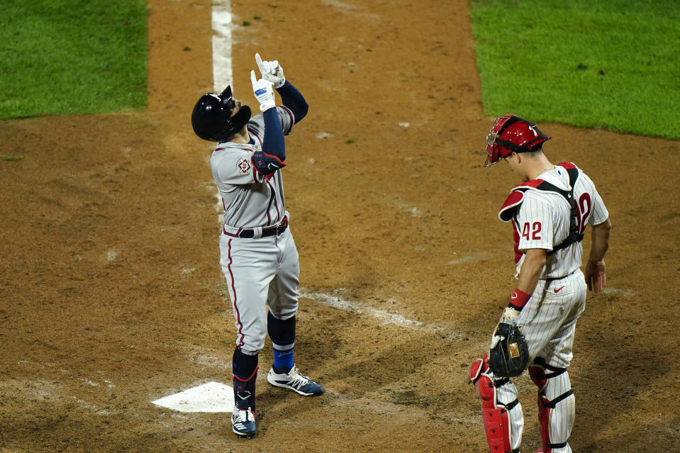 Atlanta Braves' Ender Inciarte, left, reacts past Philadelphia Phillies catcher J.T. Realmuto after hitting a home run off pitcher Adam Morgan during the seventh inning of a baseball game, Friday, Aug. 28, 2020, in Philadelphia. (AP Photo/Matt Slocum)