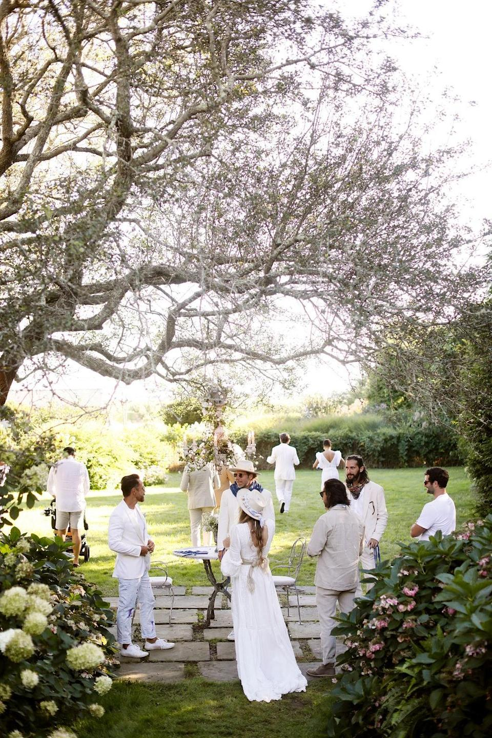 """""""One of my favorite spots is under this turn of the century pear tree that shades the pool off to the left,"""" Dean says. """"We hung an antique chandelier from one of the limbs centered over an iron French marble table where guests were able to pick up handmade <a href=""""https://www.instagram.com/campisidro/?hl=en"""" rel=""""nofollow noopener"""" target=""""_blank"""" data-ylk=""""slk:Camp Isidro"""" class=""""link rapid-noclick-resp"""">Camp Isidro</a> indigo dyed linen masks."""""""