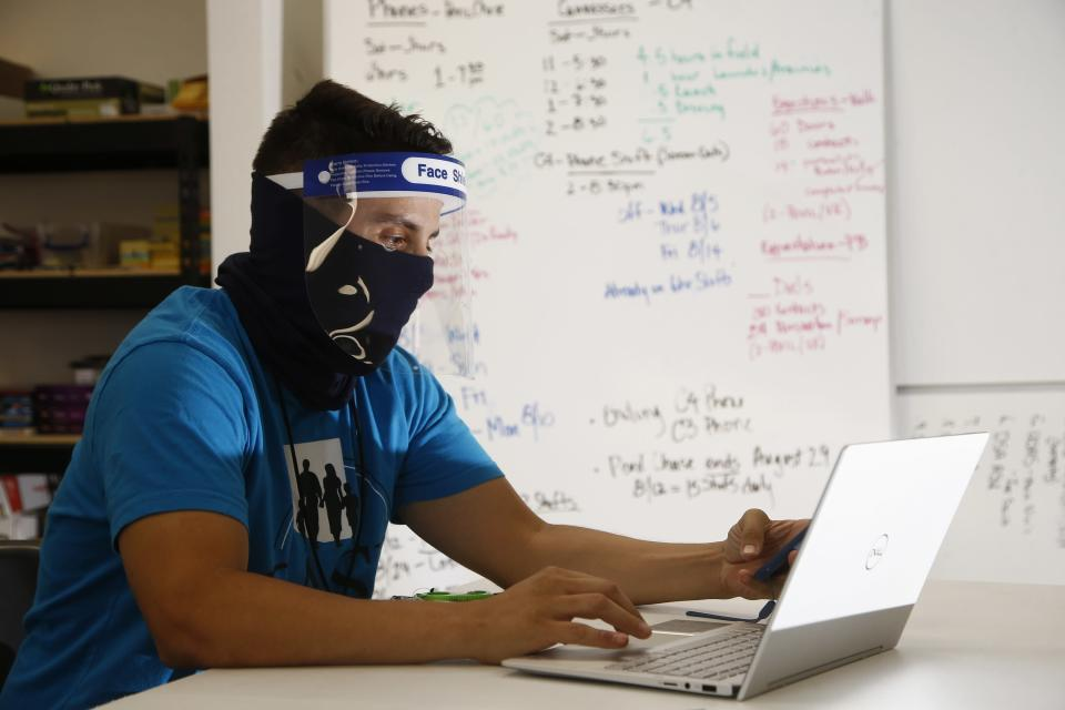 FILE - In this Aug. 6, 2020 file photo wearing a face covering and face shield while working amid the coronavirus, Maico Olivares, lead voter registration organizer for Central Arizonans for a Sustainable Economy, works his phone and computer as he tries to reach about 25 people a day, mostly within the Latino community, to persuade them to register to vote, in Phoenix. Immigrant-rights and grassroots organizations that have been mobilizing Latinos in Arizona for nearly two decades helped propel Joe Biden to victory in a traditionally conservative state. (AP Photo/Ross D. Franklin,File)