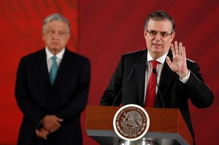 Mexico's Foreign Minister Marcelo Ebrard holds a document as Mexico's President Andres Manuel Lopez Obrador looks on during a news conference at National Palace in Mexico City