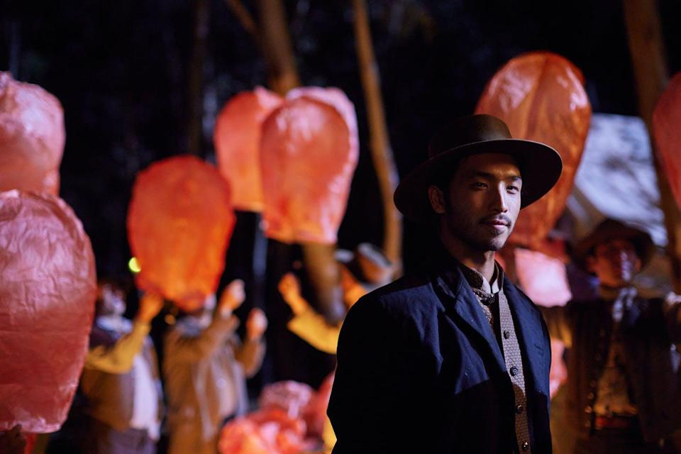 A Chinese man stands amid red lanterns