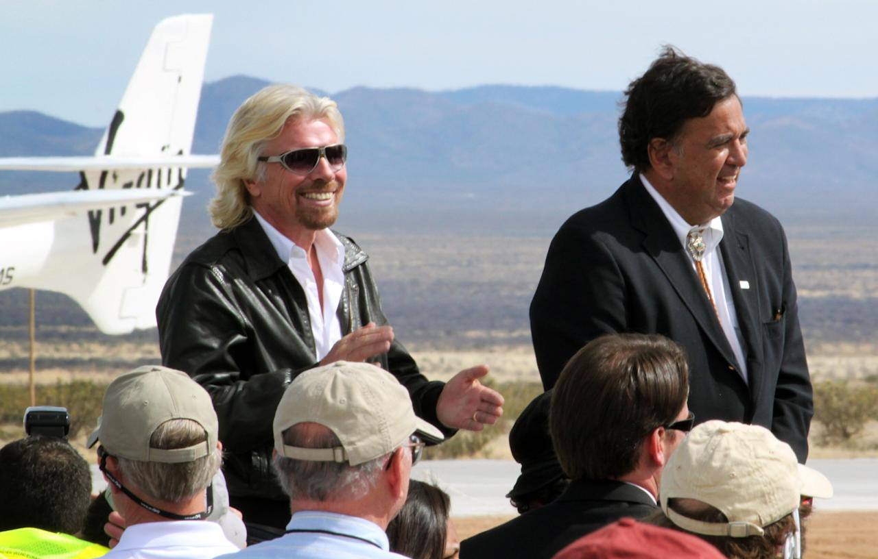 In this Oct. 22, 2010, image, Virgin Galactic founder Richard Branson, left, claps during a runway dedication ceremony at Spaceport America in Upham, N.M. Branson has vowed to be one of the first passengers when Virgin Galactic begins commercial space tourism flights from the spaceport.