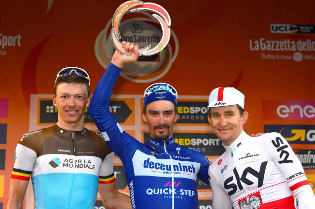 French rider Julian Alaphilippe, center, celebrates his victory on podium with runnerup Oliver Naesen, left, and third placed Michal Kwiatkowski after the 291-kilometer (181-mile) route along the Italian Riviera for the 110th edition of the Milano-Sanremo cycling classic, in Sanremo, Italy, Saturday, March 23, 2019. (Dario Belinghieri/ANSA via AP)