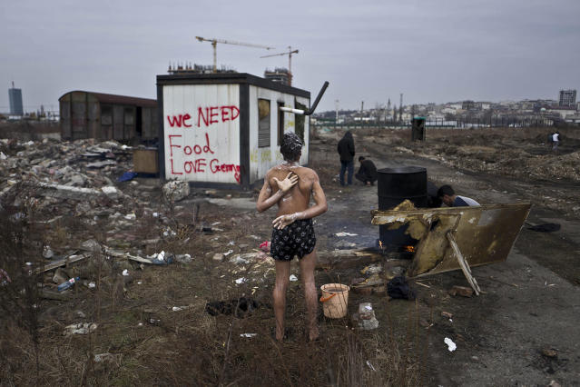 <p>Unaccompanied minor, a migrant from Afghanistan, showers on a cold day near an old train carriage where he and other migrants took refuge in Belgrade, Serbia on Feb 11, 2017. (Photo: Muhammed Muheisen/AP) </p>