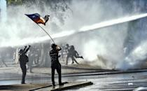 Demonstrators are sprayed by a riot police water cannon during a protest against Chilean President Sebastian Pinera's government in Santiago on October 30, 2020