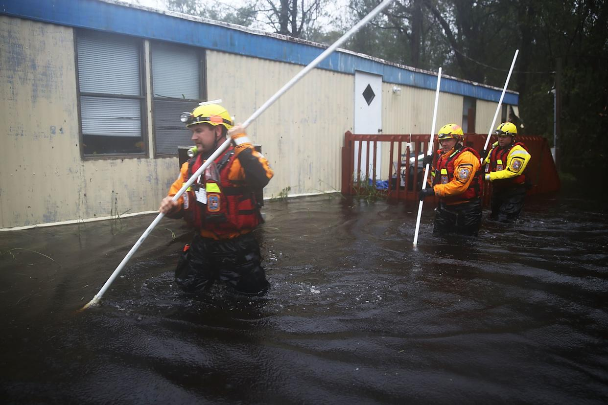 Boone County Fire Rescuers check for occupants in a home surrounded by floodwatersinBolivia.