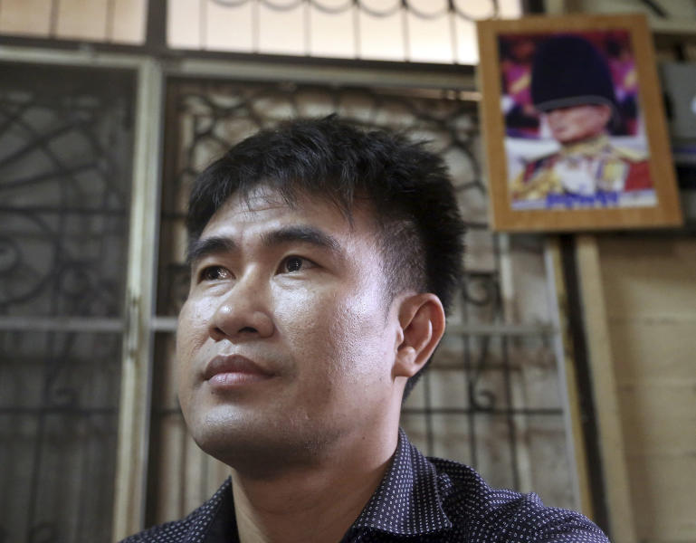 "In this photo taken Sept. 10, 2013, Thanawat Martnok poses for photographer with the photo of King Bhumibol Adulyadej, top, displayed at his house in Bangkok, Thailand. After having quarreled with his younger brother Yuthapoom Martnok, Thanawat told police that Yuthapoom had defamed King Bhumibol, an accusation that should be punished up to 15 years behind bars. Yuthapoom was indicted on charges of ""lese majeste"" - insulting the royal family. Denied bail on national security grounds, he has been jailed for a year in a Bangkok prison where he is anxiously awaiting the court's verdict Friday, Sept. 13, 2013. (AP Photo/Apichart Weerawong)"